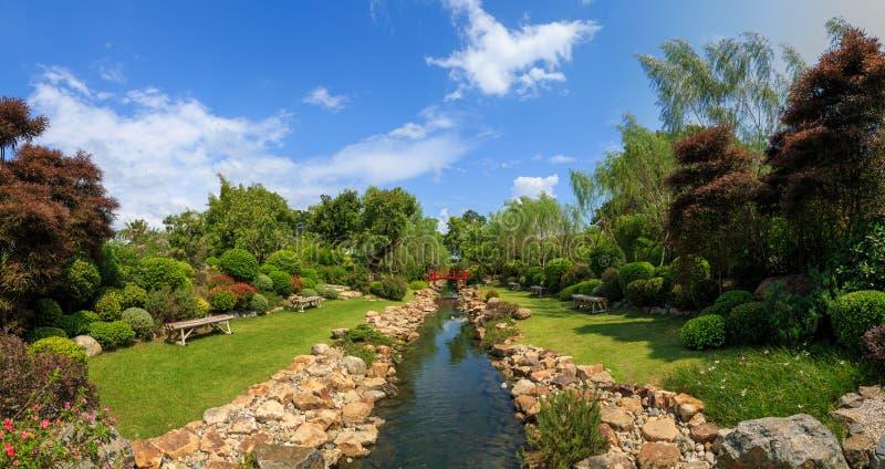 Japanse tuin met kanaal en rode brug stock afbeelding