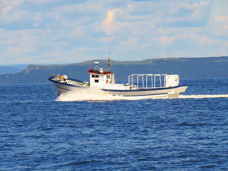Japanse vissersboot die zich snel in blauwe overzees in zonnige de herfstdag bewegen stock foto's