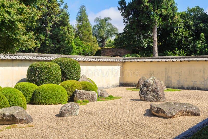 Japanse zentuin die door muur wordt omringd stock afbeelding