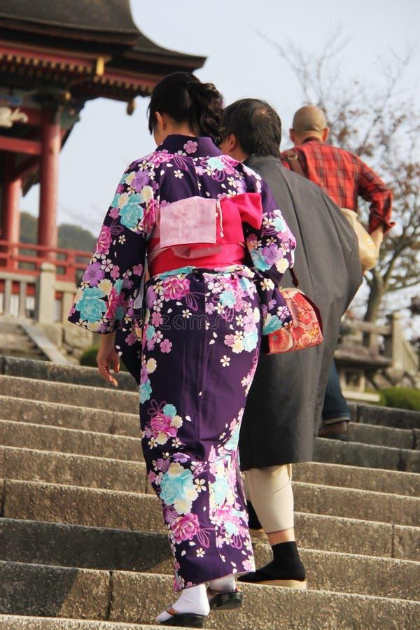 Japansk dam i kimono som klättrar trappa till den Kiyomizu-dera templet, Kyoto royaltyfria bilder