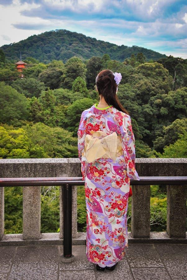 Japansk flicka som beskådar en tempel på den skogsbevuxna backen arkivfoto