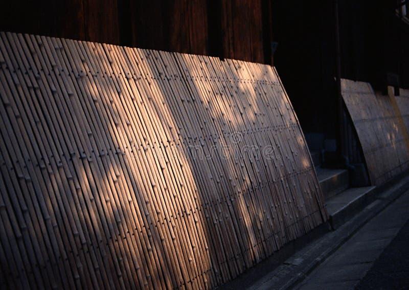 Japansk fortsatt bambuvägg med solstrålar arkivfoto