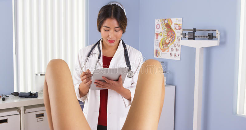 Japansk gynekolog med patienten i examenrum arkivbild