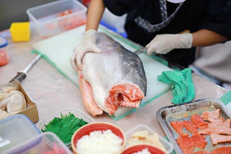 Japansk kock som skivar den rå fisken för laxsushi Kock som f?rbereder en ny lax p? en sk?rbr?da arkivfoto