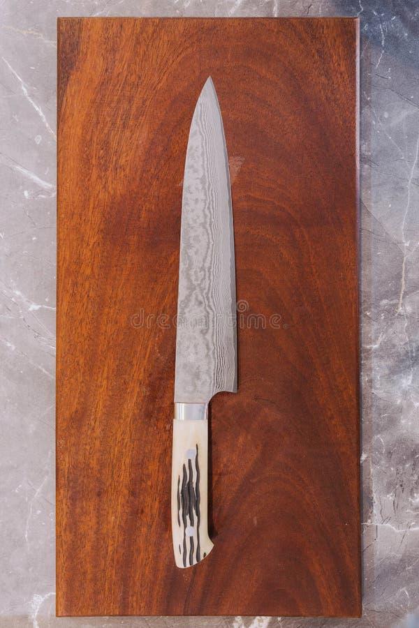 Japansk kocks modell för våg för blad för knivrostfritt stål, textur för kniv för Damascus stilkök på träskärbräda arkivbilder