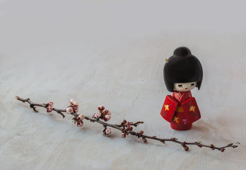 Japansk kokeshidocka och kvist av körsbärsröda blomningar arkivfoton
