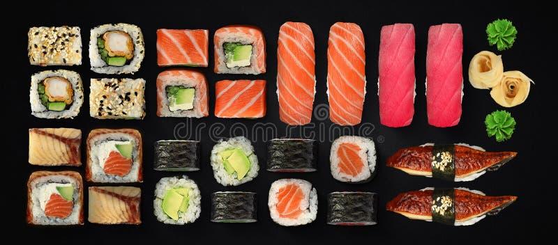 Japansk kokkonst Sushi- och rulluppsättning över mörk bakgrund royaltyfria bilder