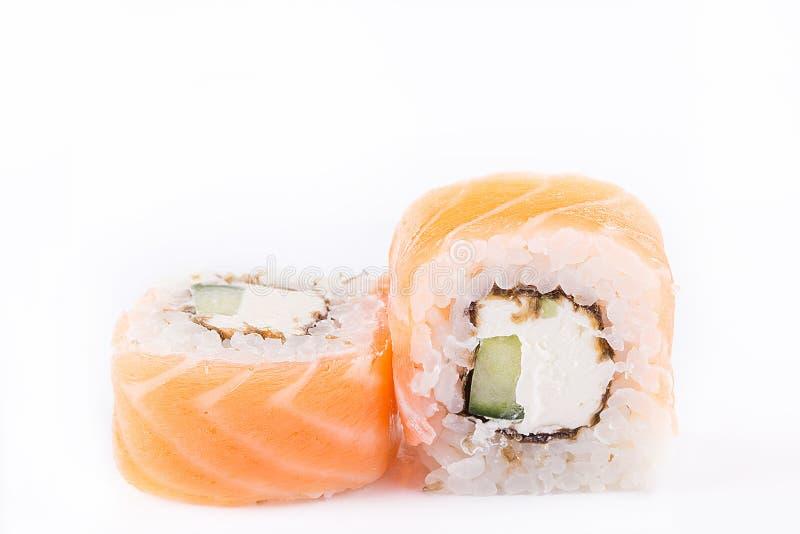 Japansk kokkonst, sushiuppsättning: laxrulle med gurkan och ost på en vit bakgrund fotografering för bildbyråer