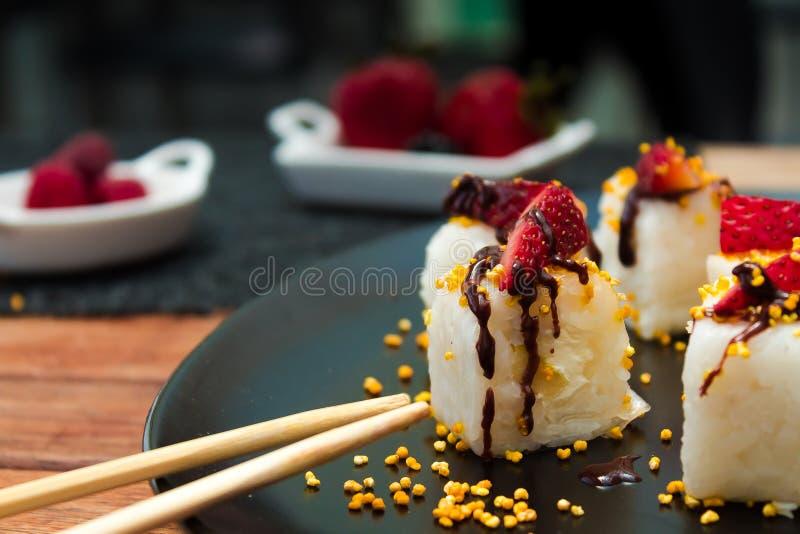 Japansk kokkonst tjänade som på en svart platta med mat på bakgrunden arkivfoto