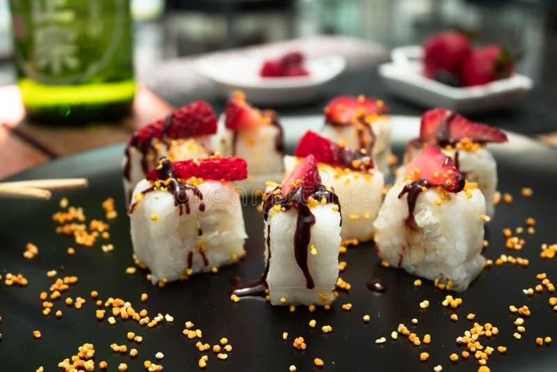 Japansk kokkonst tjänade som på en svart platta med mat och drycken på bakgrunden arkivbilder