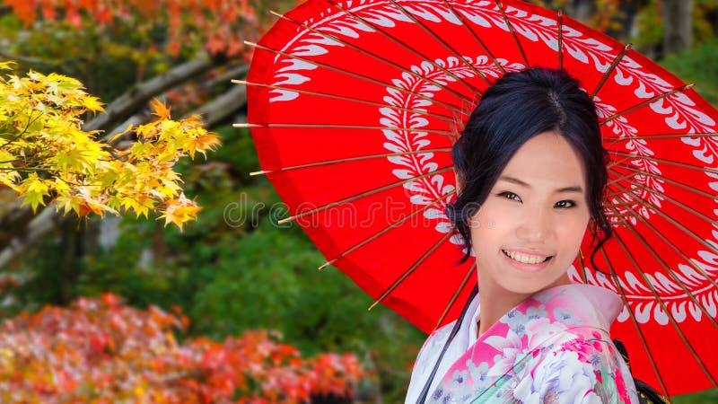 Japansk kvinna i en japansk trädgård i höst arkivbild