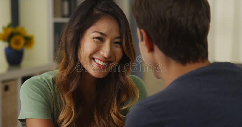 Japansk kvinna som ler och talar till pojkvännen arkivfoto