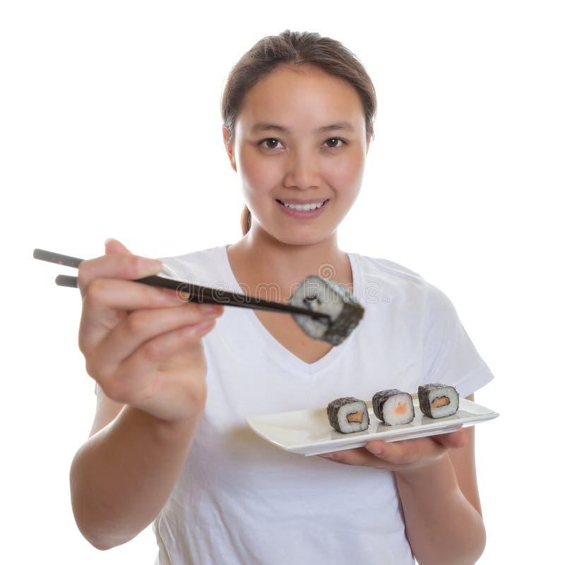 Japansk kvinna som smakar nya sushirullar fotografering för bildbyråer