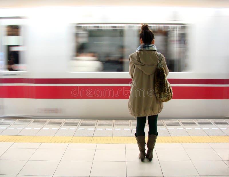 Japansk kvinna som väntar på drevet i den Tokyo gångtunnelen royaltyfri foto