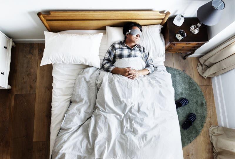 Japansk man som sover på säng med ögonmaskeringen arkivbild