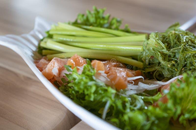 Japansk mat, laxsashimi med havsväxt och grönsaker i Cer arkivfoto