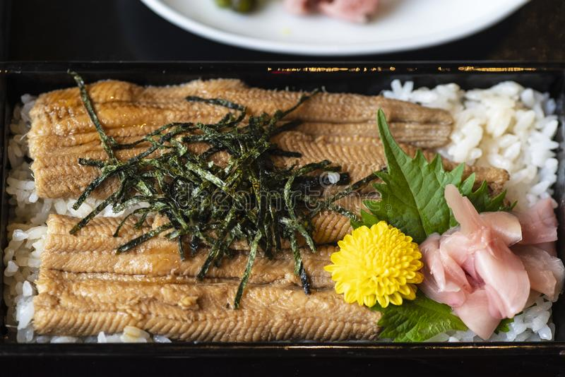Japansk maträtt grillad fisk Lång Unagi för hackor nigiri eller sushi från den svarta plattan, japansk traditionell mat arkivbilder