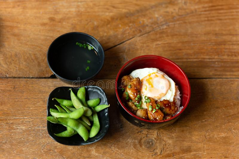 Japansk matuppsättning av teriyakihöna med ris och det stekte ägget i en bunke arkivfoton
