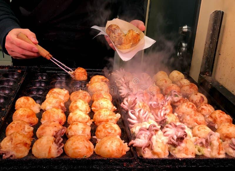 Japansk mellanmålgatamat, takoyaki i varm panna arkivbild