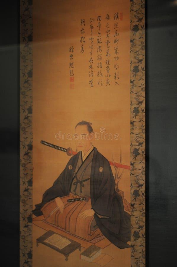 Japansk person på konstarbetet En grabb på bilden bär den japanska traditionella klänningen och har det japanska svärdet Katana I fotografering för bildbyråer