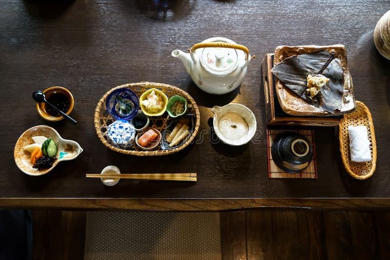Japansk ryokan frukostaptitretaredisk inklusive mentaikoen, knipa, havsväxt, bambufors, varm platta, andra sidandisk royaltyfri foto