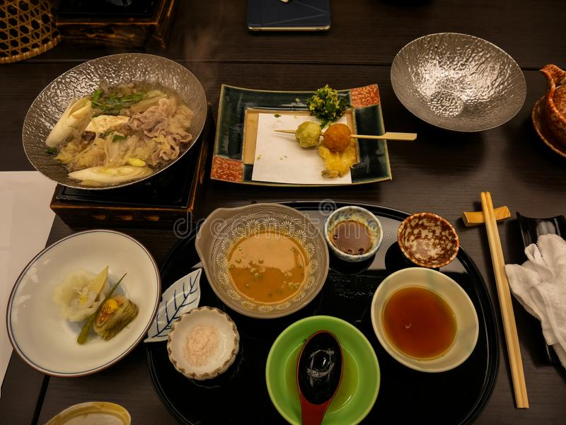 Japansk ryokan kaisekimatställevarmrätt inklusive den varma krukan för grisköttshabu, variation av grönsaker, med salt och sesamv arkivbilder