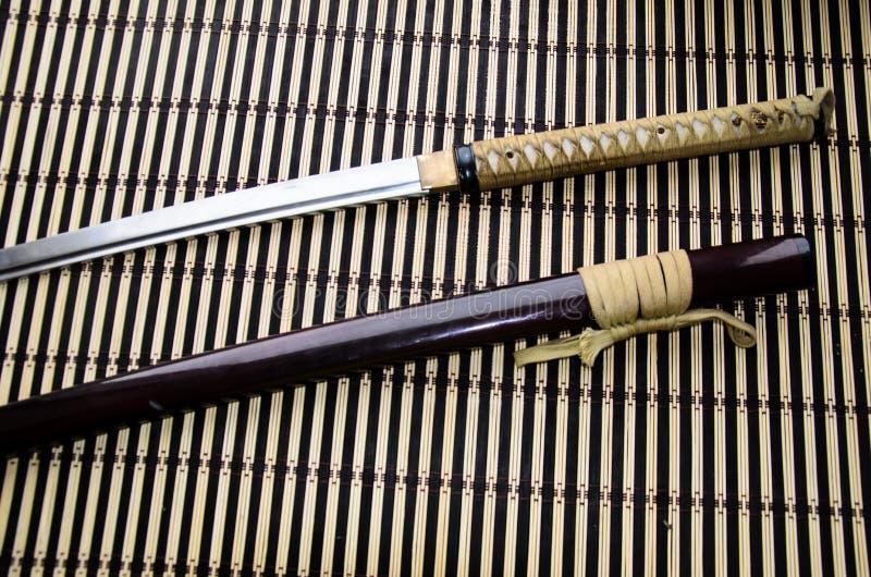 Japansk svärdkatana och skida på matt bambu royaltyfri fotografi
