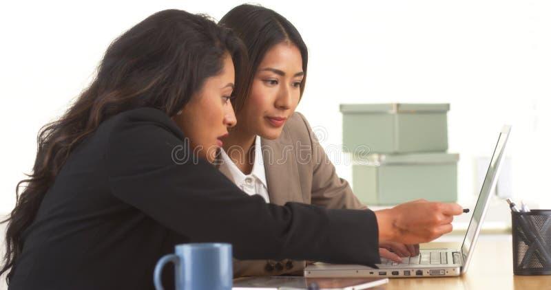 Japanska och mexicanska affärskvinnor som arbetar på bärbara datorn royaltyfri bild