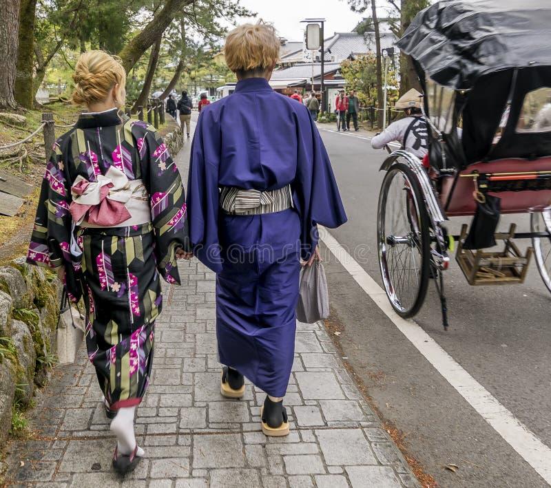 Japanska par i traditionell kläder som går ner gatan nära en rickshaw i Kyoto, Japan fotografering för bildbyråer