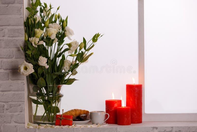 Japanska rosor i en vas av vatten bredvid en röd levande ljusfrukost och en gåva på fönsterbrädan royaltyfria bilder
