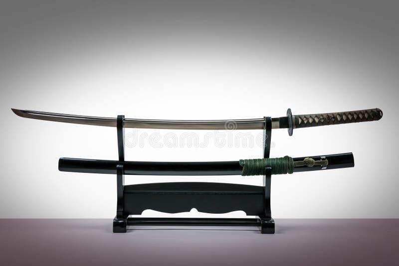 Japanskt iaidosvärd i svart träställnings- och vitbakgrund royaltyfria bilder