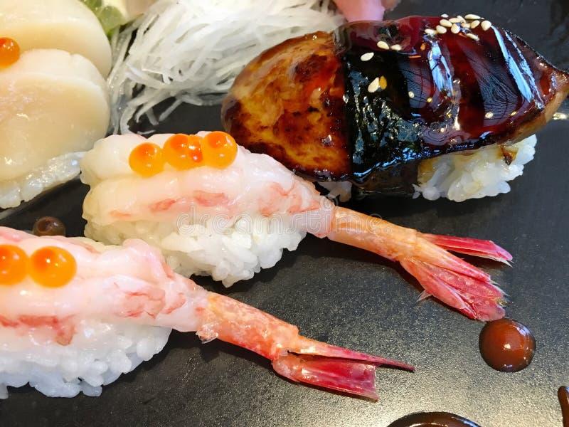 Japanskt mål med många sorter av sushi på svart maträtt arkivfoto
