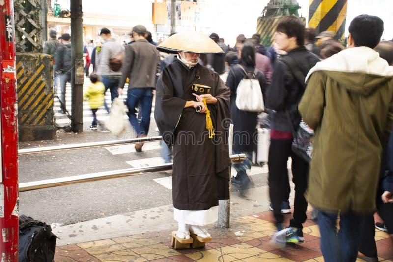 Japanskt munkanseende för att motta för att donera från japanskt folk och utländska handelsresande i den Ameyoko marknaden på Uen arkivbild