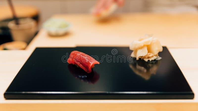 Japanskt Omakase mål: Otoro BluefinTuna Sushi betjänad av hand med den inlagda ingefäran på den glansiga svarta plattan Japanskt  fotografering för bildbyråer
