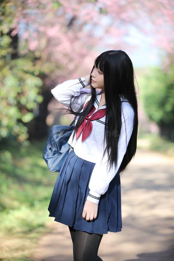 Japończyk dziewczyny szkolna suknia z Sakura kwiatu naturą zdjęcia royalty free