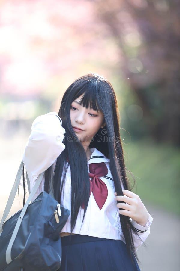 Japończyk dziewczyny szkolna suknia z Sakura kwiatu naturą zdjęcie stock