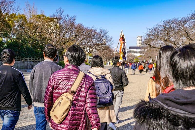 Japończyk, turyści, podróżnicy chodził wokoło Osaka kasztelu parka w Mar 2018 z suchym drzewem wokoło, Oaska, Japonia zdjęcie royalty free