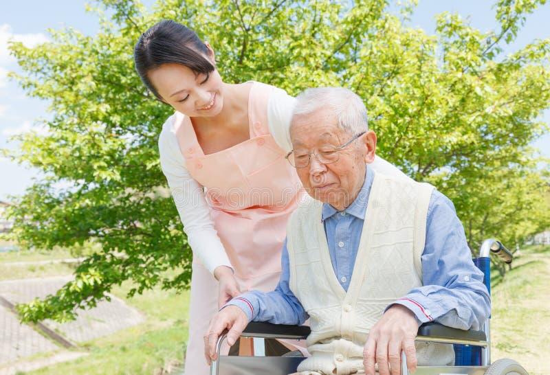 Japońscy opiekuny i senior w śródpolnym opiekunie fotografia royalty free