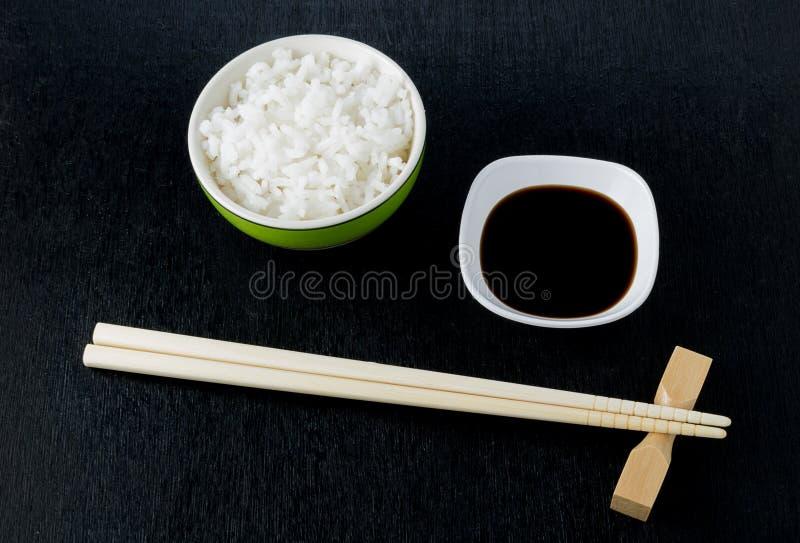 Japońscy suszi chopsticks nad soja kumberlandem rzucają kulą, ryż na czarnym bac zdjęcia stock