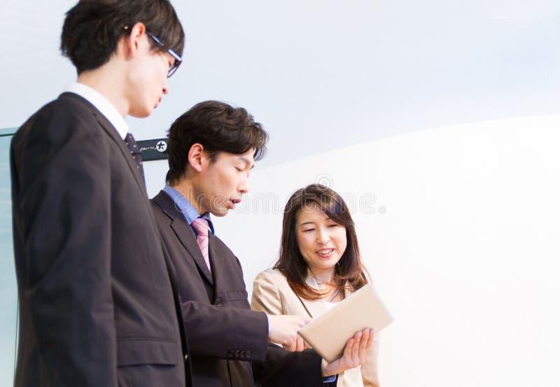 Japońska biznesowa kobieta i biznesowi mężczyzna opowiada przy biurkiem, patrzeje dokumenty na pastylka przyrządzie obraz stock
