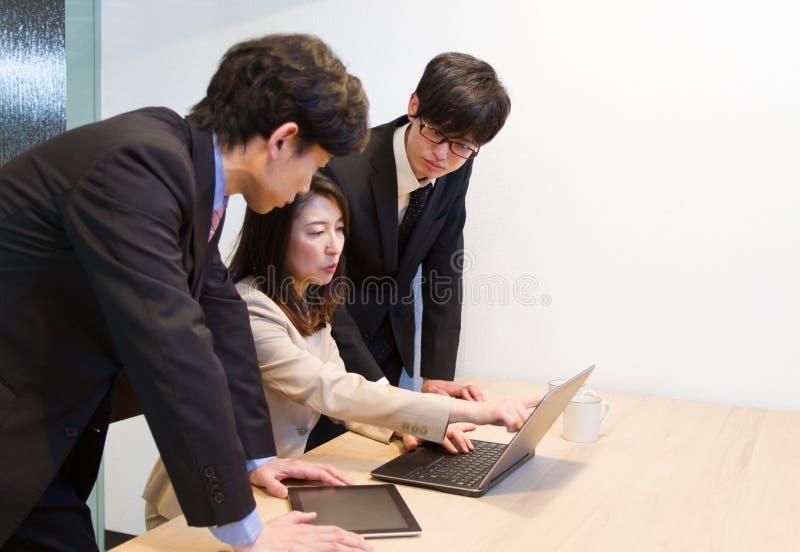 Japońska biznesowa osoba dyskutuje, patrzejący internet strony internetowe i dokumenty na pececie obraz stock
