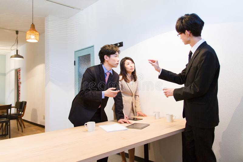 Japońska biznesowa osoba dyskutuje przy biurkiem, z pastylka przyrządem zdjęcia royalty free