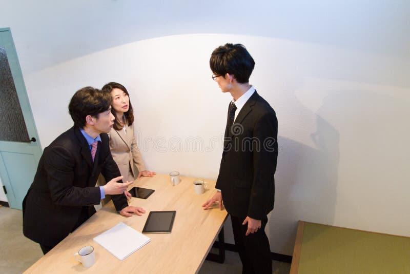 Japońska biznesowa osoba opowiada, patrzejący dokumenty na pastylka przyrządzie na biurku fotografia royalty free
