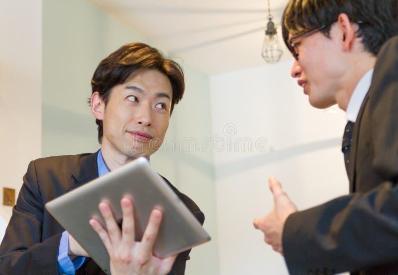 Japońska biznesowa osoba opowiada z kolegą, pokazuje dane z pastylka przyrządem zdjęcia stock