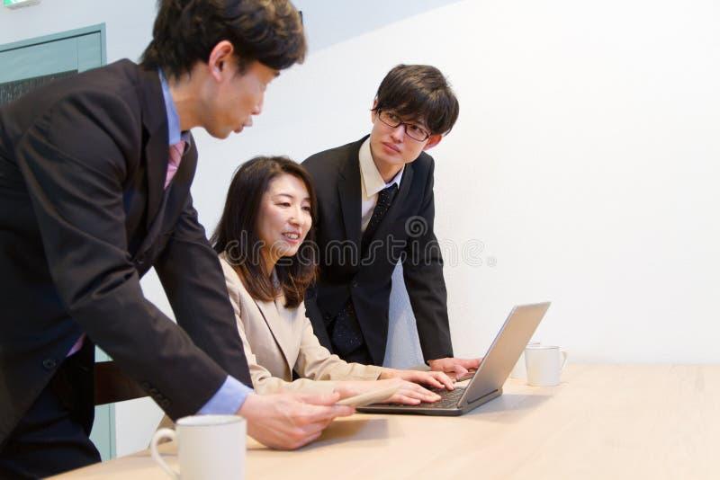 Japońska biznesowa osoba patrzeje internet zawartość na pececie fotografia royalty free
