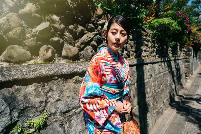 Japońska dama relaksuje polegać na kamiennej ścianie obrazy stock