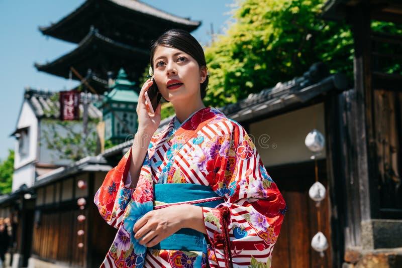 Japońska dziewczyna dzwoni przyjaciela ono modlić się wpólnie obraz stock