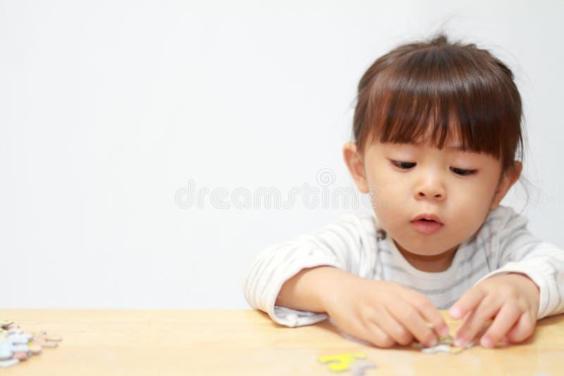 Japońska dziewczyna robi wyrzynarki łamigłówce obraz stock