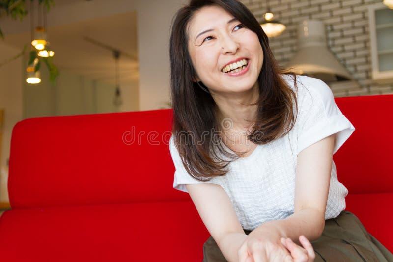 Japońska kobieta śmia się przy żywym pokojem, siedzi na czerwonej kanapie obrazy royalty free