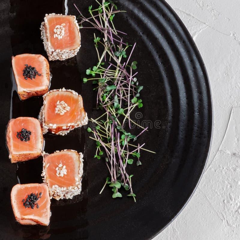 Japoński łososiowy Tataki z sezamem i flancami świezi ziele Na czarnym glina talerzu Makro- fotografia, zakończenie zdjęcie stock
